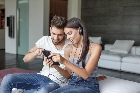 escuchando musica: Pareja joven escuchar música en sofá en el interior, la selección de la música en la tableta, tecnología inalámbrica Foto de archivo