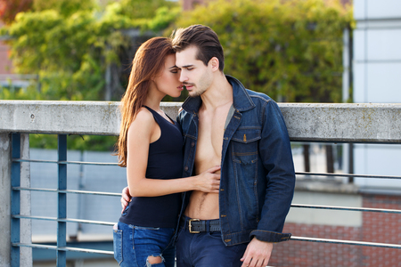 Sensual young couple posing outdoor, brunette woman seduce man, whispering