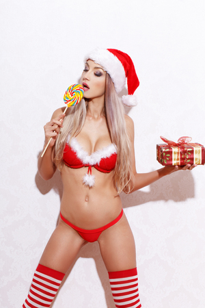 sex santa: Sexy blonde woman in santa hat licking lollipop, Christmas