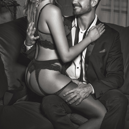 Sexy woman lover in underwear sit on rich man in night club, foreplay, black and white Stock Photo
