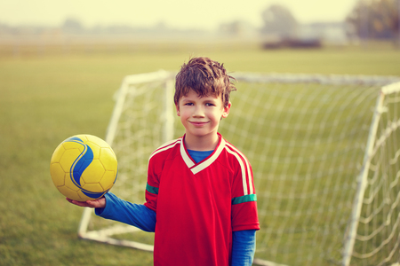 Happy little soccer player boy holding ball on field, outdoor