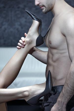 Woman legs in high heels playing on sexy man body closeup