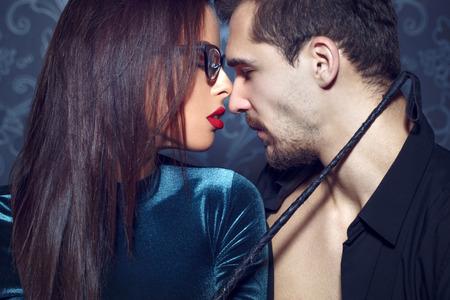 Sexy femme MILF dominante dans les verres, les lèvres rouges, fouet tenant à l'amant jeune, sensualité, bdsm