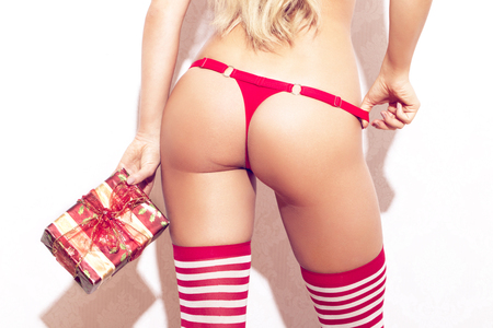 Sexy woman holding gift box rear view, ass in red panties Standard-Bild