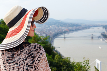 sightsee: Young woman in hat enjoying Budapest panorama, Hungary