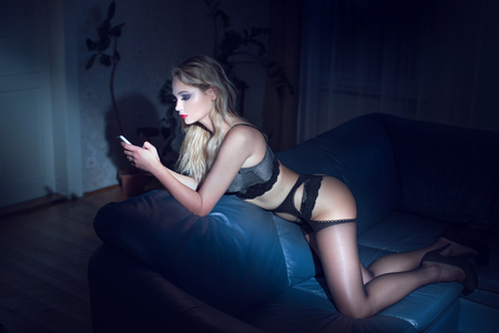sex cell: Sexy blonde woman in underwear sending blackmail or message Stock Photo