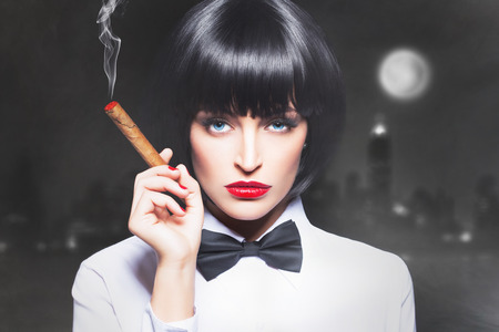 Sexy mafiosi woman boss in tux smoke with cigar in town Stock Photo