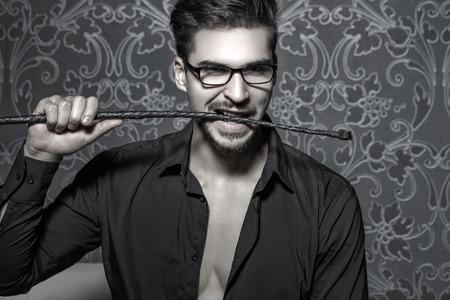 desnudo masculino: Inteligente y guapo látigo de la mordedura del hombre en la noche, BDSM