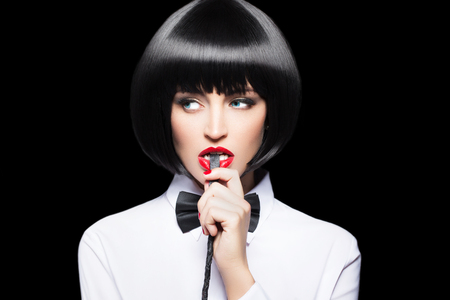 Sexy femme avec des lèvres rouges dans morsure perruque fouet portrait, bdsm, isolé sur noir Banque d'images