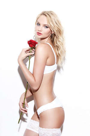 nude blonde girl: Sexy blonde woman in underwear posing with rose at white wall