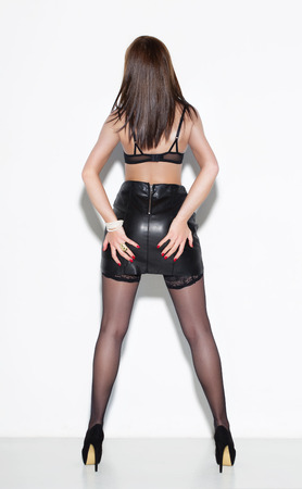 leather: Sexy fashionable woman in leather skirt and underwear grab ass at wall Stock Photo