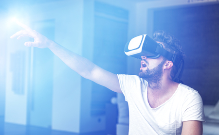 choise: Young man with VR glasses playing virtual reality with blue glowing light source Stock Photo