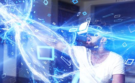 Young man with VR glasses playing virtual reality, high energy lightning media stream with particles