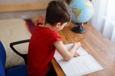elementary school: Little kid doing homework at home, filling exercise book Stock Photo