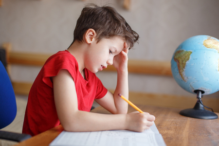 Study Desk: little schoolboy writing hard homework at home Stock Photo