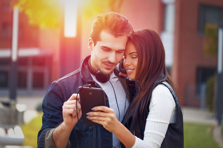 couple dating: Young couple listening music by tablet during dating