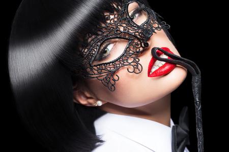 Sexy vrouw in masker, zweep op rode lippen, bdsm, geïsoleerd op zwart Stockfoto