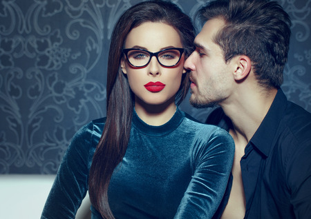 Confident sexy woman with red lips seducing young rich man Stock Photo