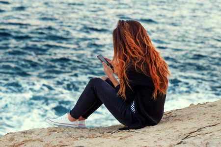 Young redhed woman with curly hair relaxing and messaging on rocky coast at sea, loneliness, wireless technology Stock Photo