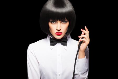 かつらと赤唇の鞭、黒の分離とポーズでセクシーなミストレス