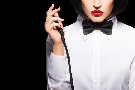 かつらと赤唇の鞭のクローズ アップ、黒の分離とポーズでセクシーなミストレス