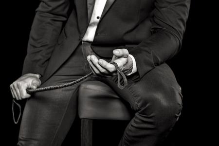 裕福な人の鞭、黒と白、bdsm を押しバーのスツールに座って