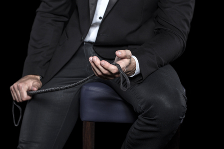 Rich man sitting on bar stool and holding whip, bdsm Stock Photo