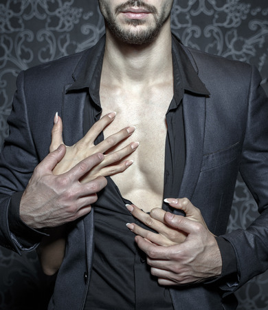 Sexy stylish rich man undressed by woman hands closeup