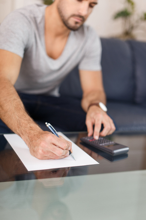 checking account: Young caucasian man doing calculation at home with calculator on blank paper