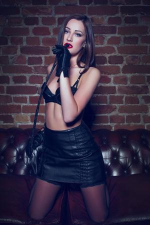 Sexy dominante vrouw knielen op bank met zweep in nachtclub Stockfoto