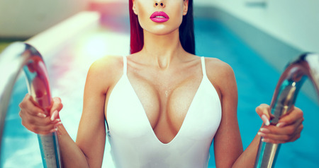 Sexy wet woman with big titis at swimming pool in sunset, color graded