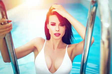 Sexy brunette vrouw met grote tieten in zwembroek poseren in zwembad in de zomer