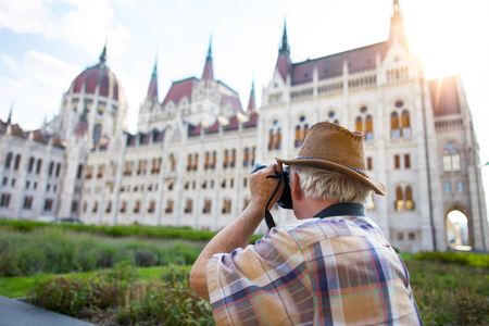 Pensioner tourist capturing Hungarian Parliament in sunset, Hungary Stock Photo