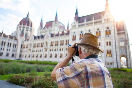 Pensioner tourist capturing Hungarian Parliament in sunset, Hungary Stok Fotoğraf