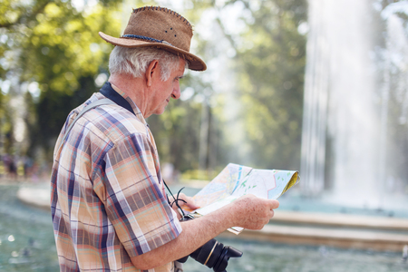 Senior tourist man searching for destination on map during trip Stock Photo