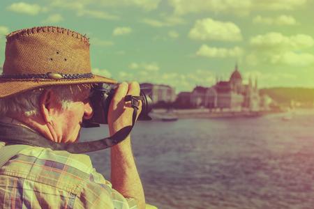 Stary turysta w kapeluszu fotografujący Budapeszt, Węgry, styl vintage
