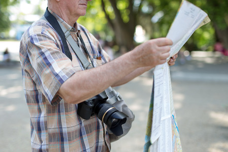 Senior tourist man with map and camera in public park during trip