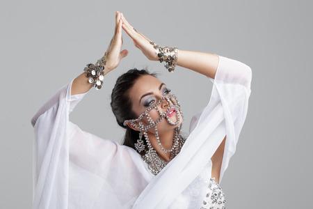 Sensual oriental dancer woman portrait with gems and veil