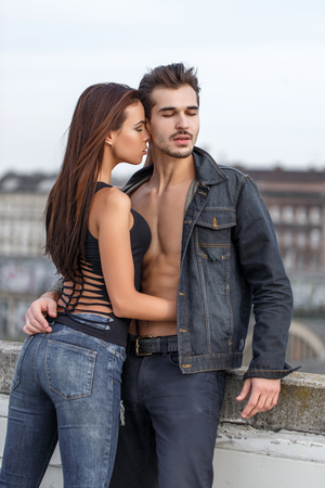 Young woman whispering love to sexy boyfriend outdoor in city Фото со стока