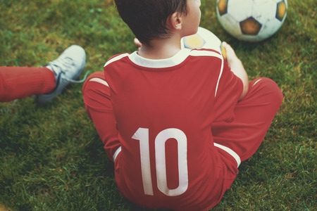 striker: Little soccer forward player boy sitting on field, training Stock Photo
