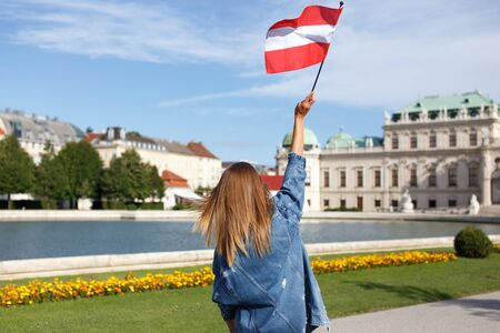 Young woman showing austrian flag in park outdoor