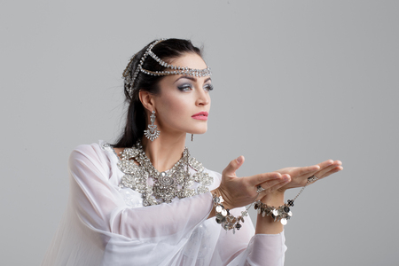 Young beautiful sensual belly dancer woman with gems dancing on grey background
