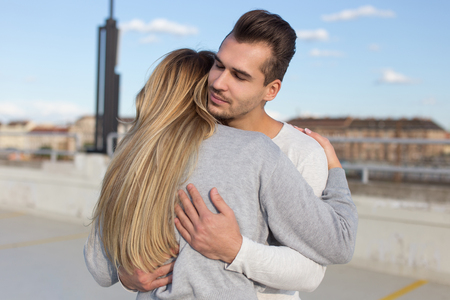 Young man cuddle girlfriend outdoors, understanding and love