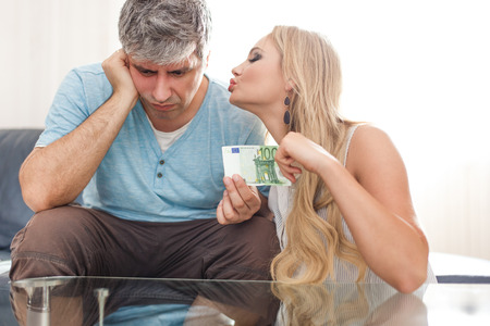 Blonde gold digger wife asking 100 Euro from sad husband, indoors