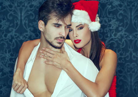 Sexy santa woman with red lips undressing macho man in white shirt indoors, Christmas surprise Stock fotó