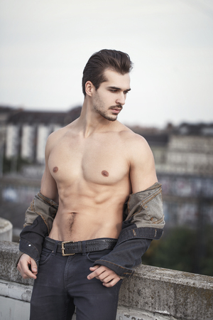 Young sexy muscular man in denim undress jacket outdoor, urban fashion