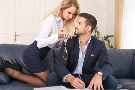 Sexy blonde secretary offering handcuffs for rich young boss in office, bdsm toy Archivio Fotografico
