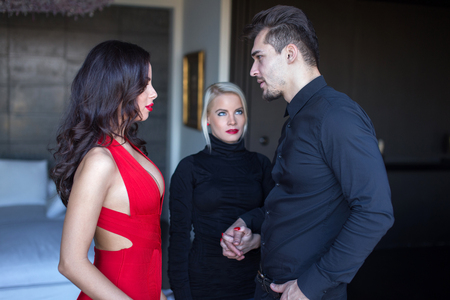 Upset blonde woman looking to disloyal boyfriend flirting with seductive woman in red dress