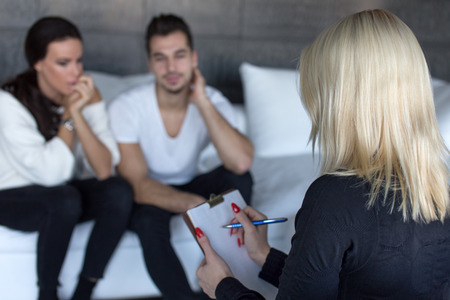 Therapist woman making notes on clipboard, couple therapy