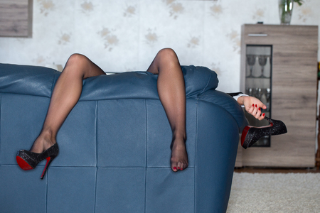 Tired woman hanging high heels after party, hangover Standard-Bild - 92881032